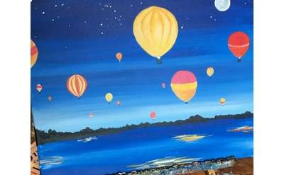 Colorful hot air balloon against a deep blue sky over Lake George