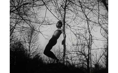 black and white movie still of person leaning against tree