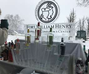 Carved Ice Sculpture with Fort William Henry Hotel logo and liquor bottles.