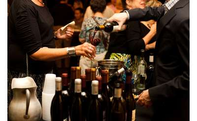person pouring wine at a wine tasting