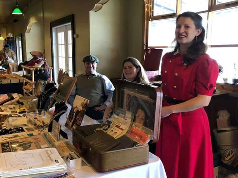 18th century dressed women and man behind a table selling historical items