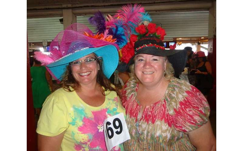 two women with colorful hats posing for the camera