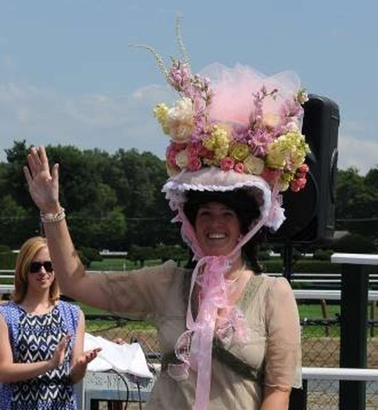 woman waving to crowd with pink roses hat