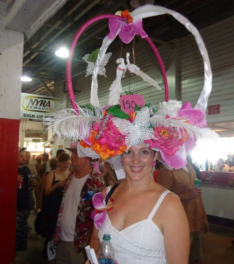 woman wearing a tall wacky hat with pink and white flowers