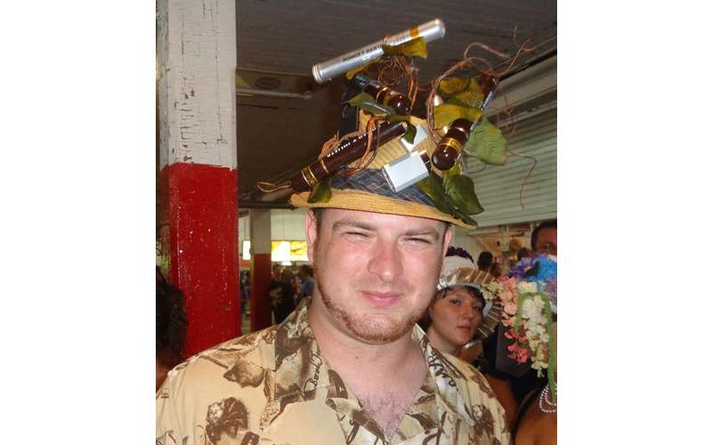 man wearing a hat covered in small objects