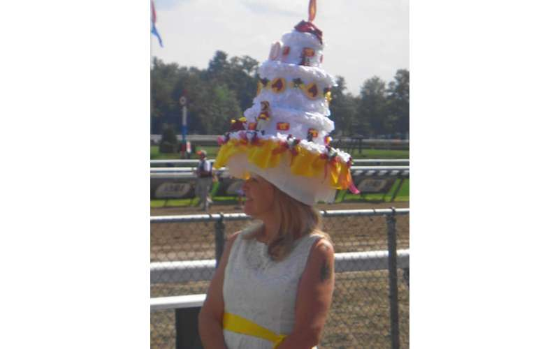 woman with a giant hat in the shape of a cake