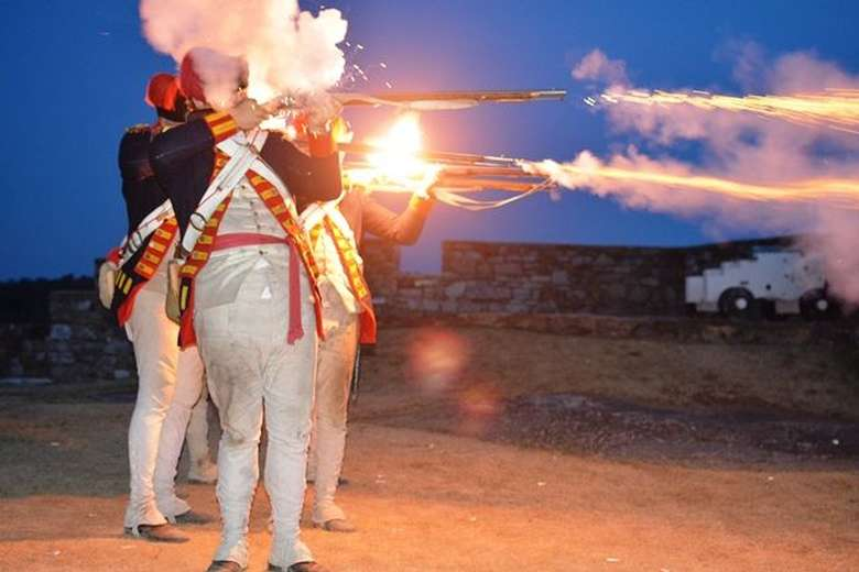 Flames spill from musket barrels as a line of soldiers fires into the night during the Fort Ticonderoga Guns by Night program.
