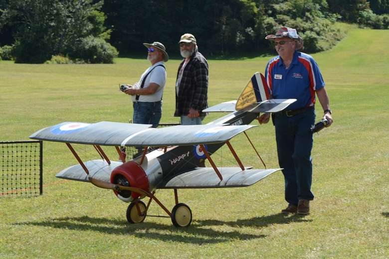 three men with a large model airplane