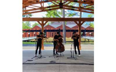 three musicians playing under a wooden structure