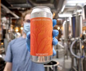 man holds up orange can of beer