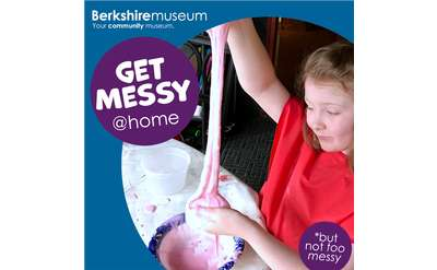 A child in a red smock stretches a gooey pink slime in her bare hands in Berkshire Museum's After-School@Home.