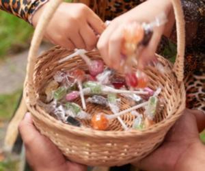hands reaching for lollipops in basket