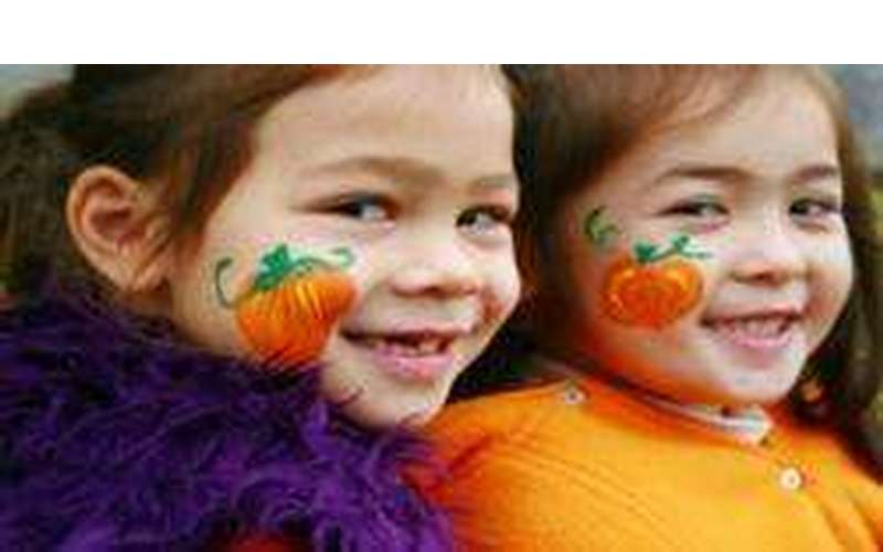 two little girls with pumpkins painted on their cheesk