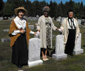 three women reenactors standing near graves