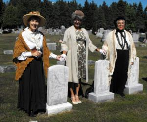 three women portraying historic figures in a graveyard