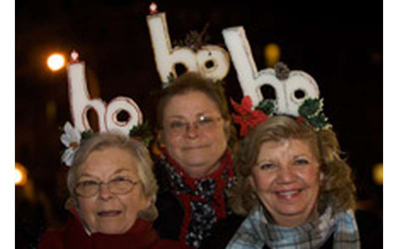 three women smiling in front of ho ho ho decorations