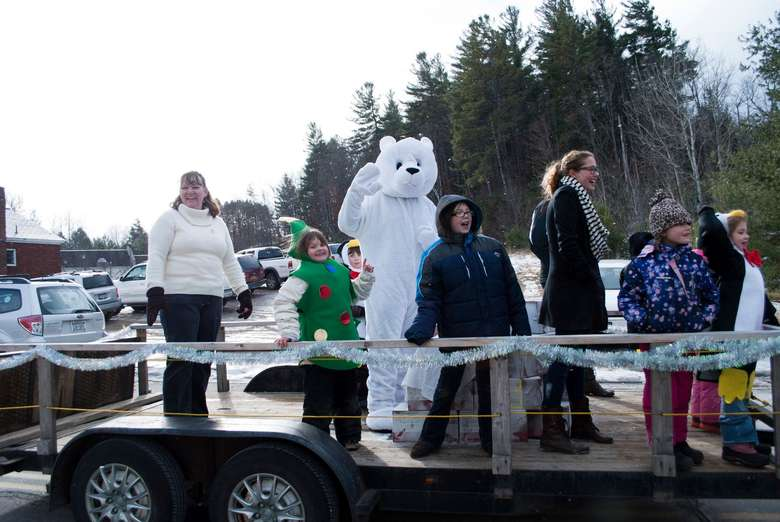 people with polar bear on float in parade