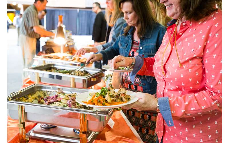 guests loading up their plates with buffet food