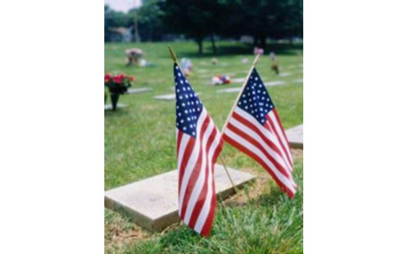 two flags in front of a gravestone