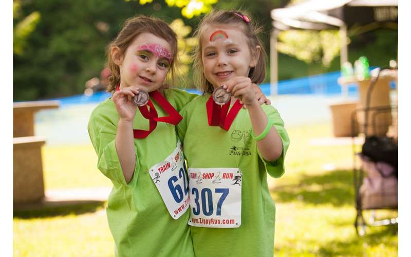 two young girls smiling and holding up race medals