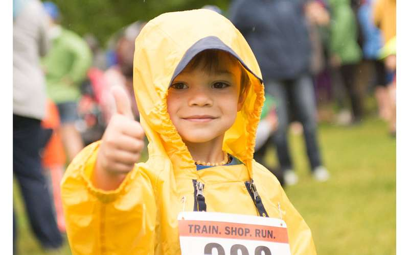 a boy in a yellow rain jacket giving a thumbs up