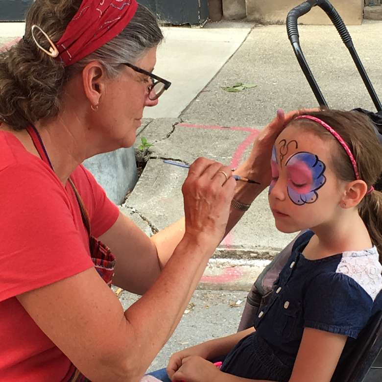 woman doing a face painting with a little girl