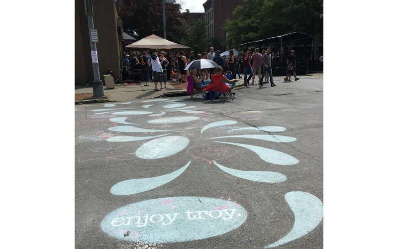 painted rain drops on cement, one says enjoy troy