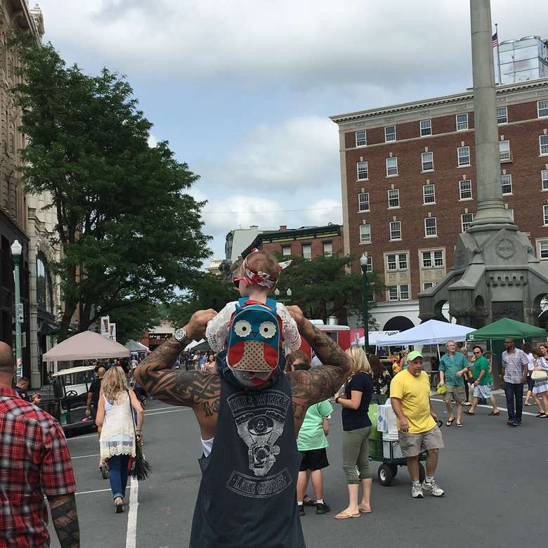 crowd, little girl with owl backpack on her dad's shoulders