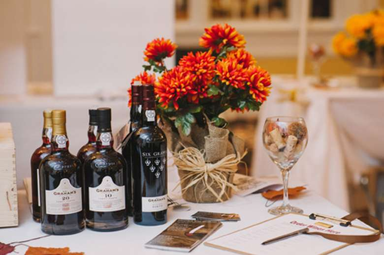 bottles of wine, glass of wine, chocolate, and flowers on a table