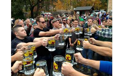 people with oktoberfest beer steins