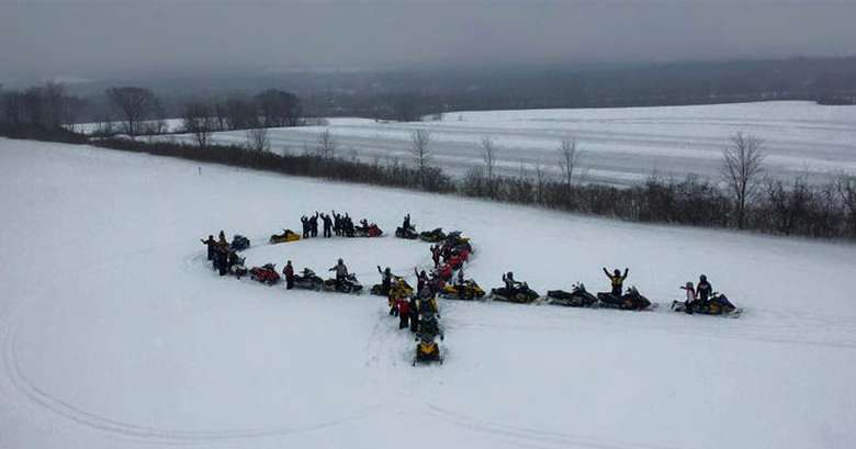 snowmobilers in the shape of a cancer ribbon