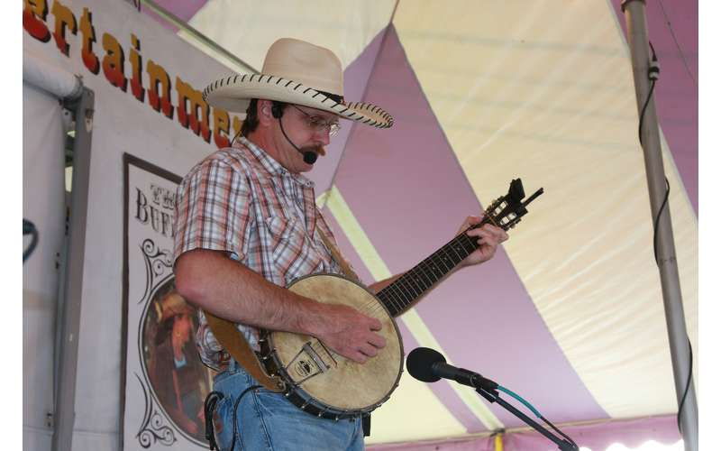 man with plaid shirt and cowboy hat performing