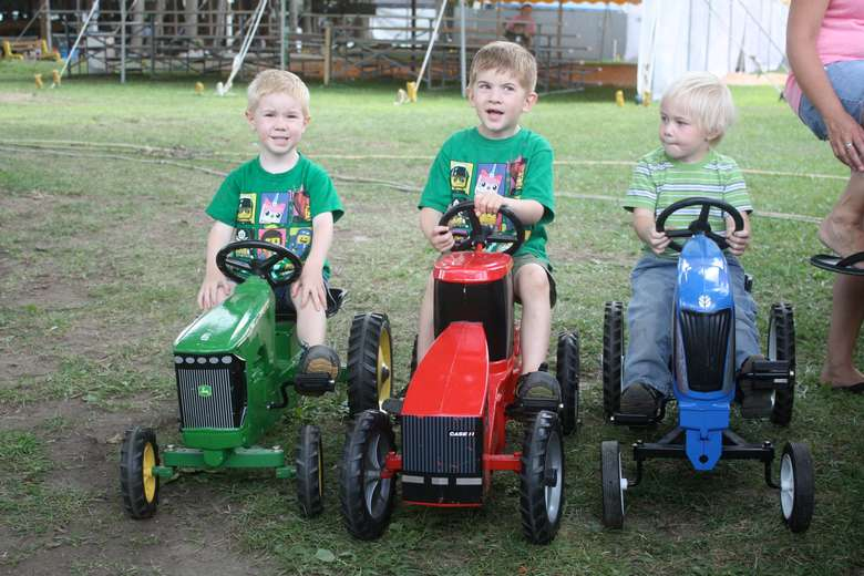 three little kids on mini tractors
