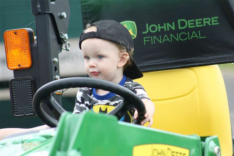 little boy on  mini tractor