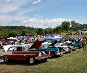 a row of classic cars on large field