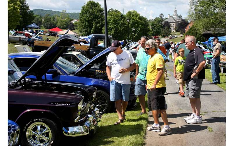 spectators looking up close at classic cars with the hoods up