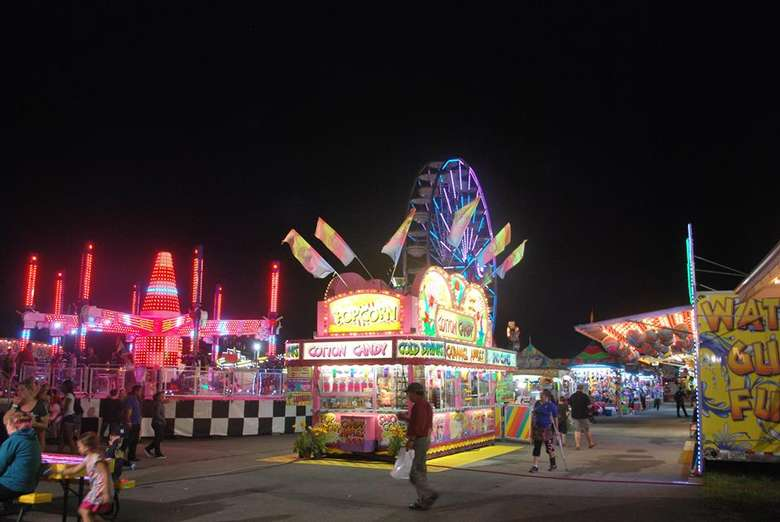 a view of food vendors during the night at a fair