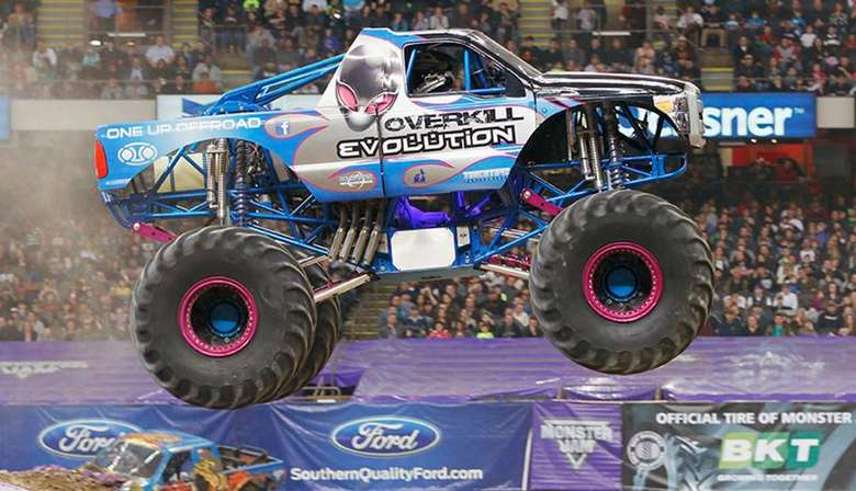 a large blue monster truck in the air