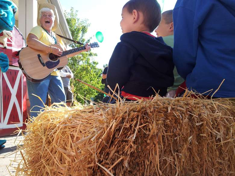 Woman plays acoustic guitar to children and families at Clifton Park Farm Fest