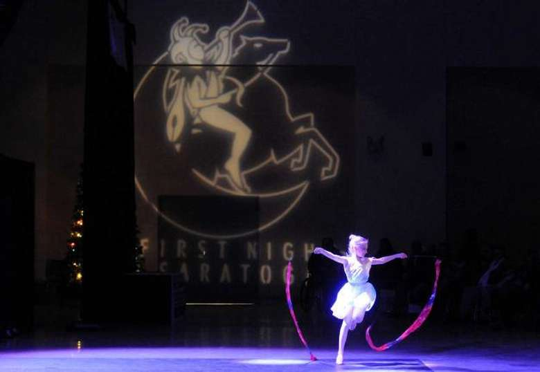 girl dancing with ribbons in front of a first night sign