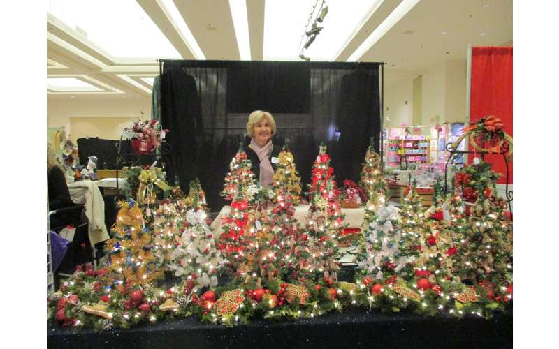 woman behind small christmas trees