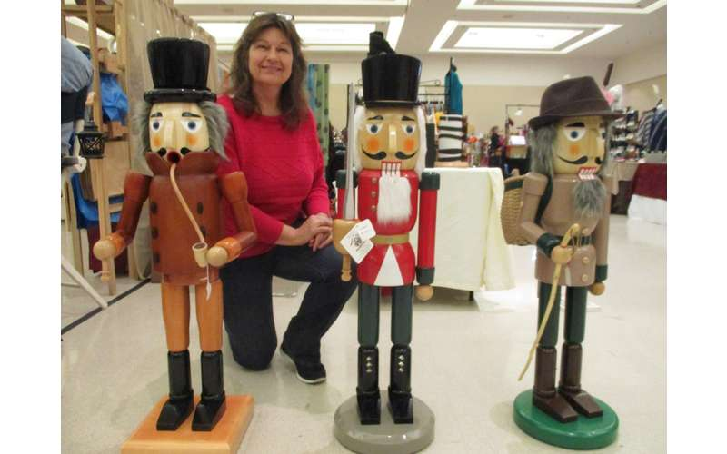 woman kneeling near wooden nutcracker dolls