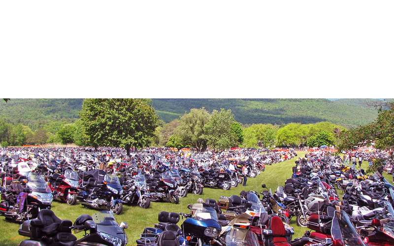 a large group of motorcycles on a grassy field