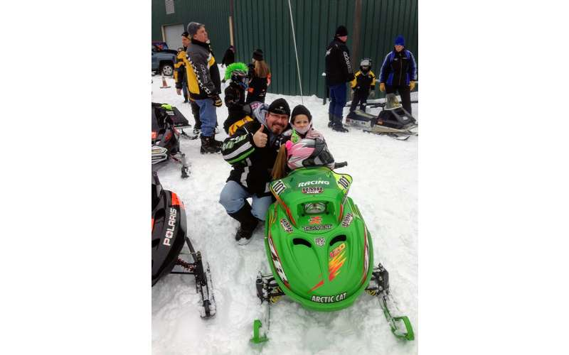 little girl on snowmobile posing with man