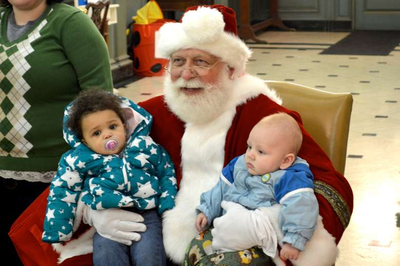 santa holding two young babies