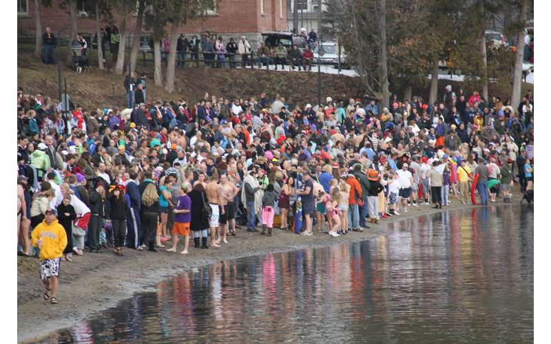 large crowd of people standing along a shoreline for a polar plunge
