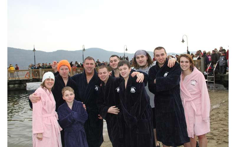 people in warm robes standing near a cold lake