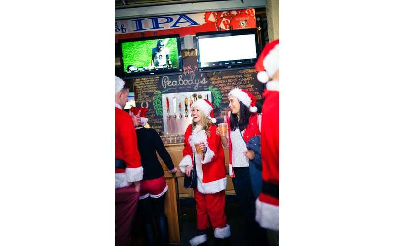 people dressed as santa in a bar