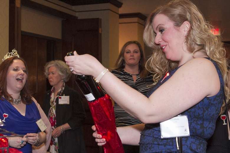 a woman opening a bottle of wine