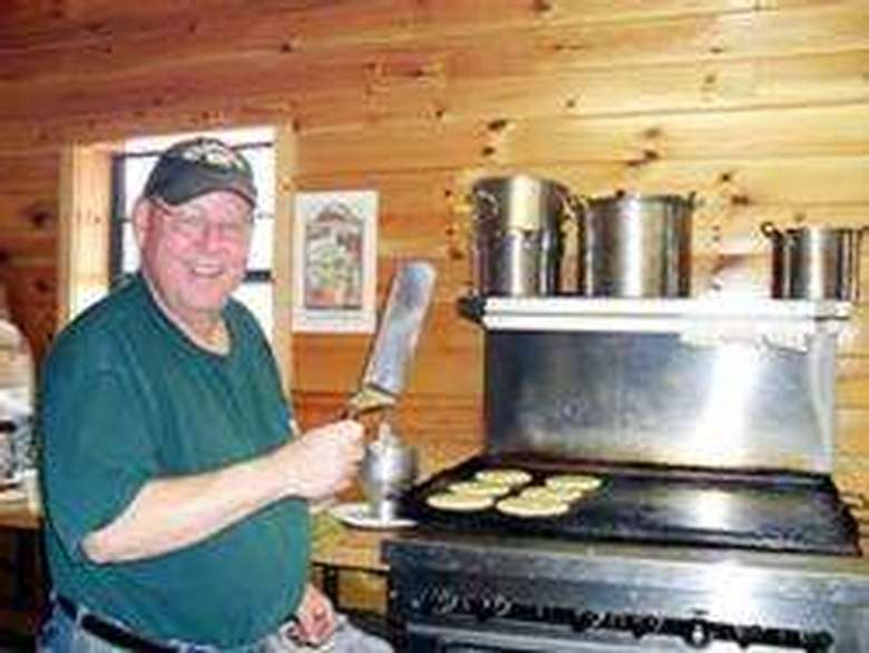 a man holding up a spatula while cooking pancakes
